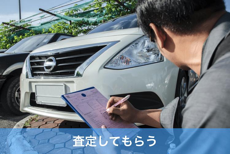 車の査定をする中年男性