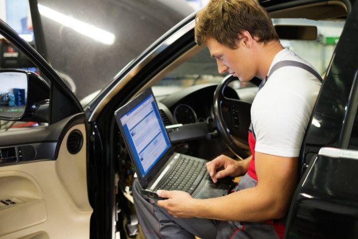 車内でパソコンを使う男性