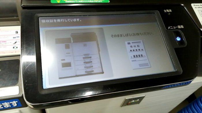 コンビニ(ローソン)店頭のファクスの操作パネル(領収証が出力中の画面)